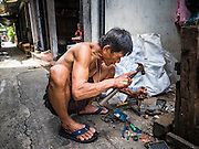 18 SEPTEMBER 2015 - BANGKOK, THAILAND: SAWAT TANGAON, 70, tears apart wall outlets looking for resellable copper wire. He lives in a home near Wat Kalayanamit and is being evicted from his home. He makes a few dollars a day scavenging wire. Fifty-four homes around Wat Kalayanamit, a historic Buddhist temple on the Chao Phraya River in the Thonburi section of Bangkok, are being razed and the residents evicted to make way for new development at the temple. The abbot of the temple said he was evicting the residents, who have lived on the temple grounds for generations, because their homes are unsafe and because he wants to improve the temple grounds. The evictions are a part of a Bangkok trend, especially along the Chao Phraya River and BTS light rail lines. Low income people are being evicted from their long time homes to make way for urban renewal.             PHOTO BY JACK KURTZ