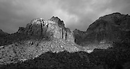 Sunlight breaks through heavy cloud cover to dramatically light the cliffs of Zion National Park
