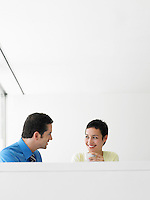 Young businessman and businesswoman conversing during coffee break