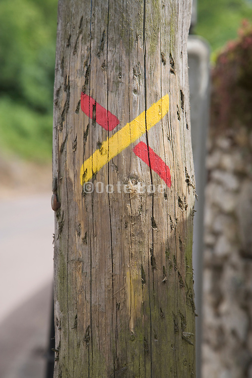 markings on a wooden post indicating direction on a rambling path France