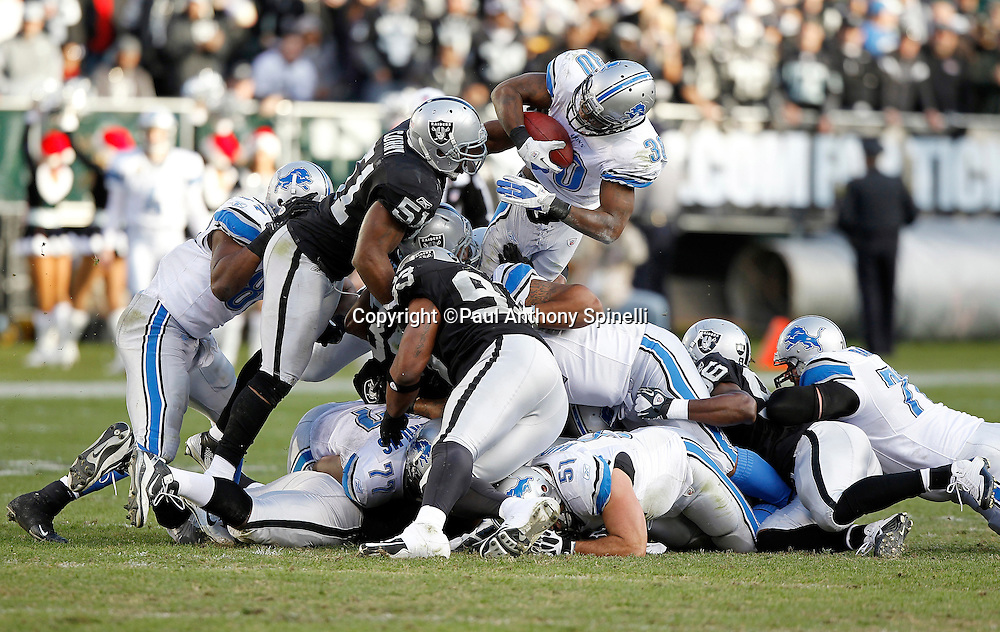 Detroit Lions running back Kevin Smith (30) dives over a pile of bodies while trying to avoid a tackle attempt by Oakland Raiders outside linebacker Aaron Curry (51) during the NFL week 15 football game against the Oakland Raiders on Sunday, December 18, 2011 in Oakland, California. The Lions won the game 28-27. ©Paul Anthony Spinelli