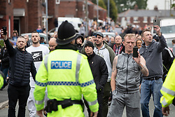 © Licensed to London News Pictures . 18/05/2019. Oldham, UK. Police push back supporters of Yaxley-Lennon after bottles, bricks and eggs are thrown by both sides at each other and fights break out . Former EDL leader Stephen Yaxley-Lennon (aka Tommy Robinson ) continues his campaign for a seat in the European Parliament representing the North West of England , by visiting Oldham . Photo credit: Joel Goodman/LNP