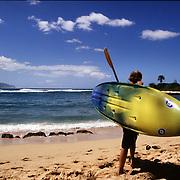 A kayaker carries his gear near Hale'iwa (Haleiwa) Beach on the North Shore of the island of Oahu, Hawaii.