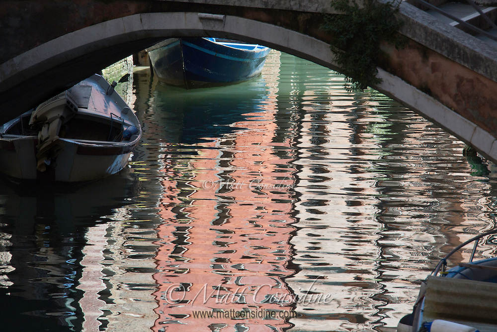 Reflections under a bridge of the pastel colored buildings and boats. (Photo by Travel Photographer Matt Considine)