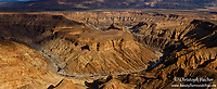 A panorama of Namibia's magnificent Fish River canyon, portraying the canyon's sharply curving ravines and multifaceted rock faces.