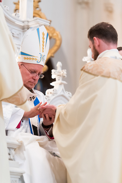 DENVER, CO - MAY 13: Denver Archbishop Samuel Aquila anoints the hands of Francesco Basso with Sacred Chrism during his ordination to the priesthood at the Cathedral Basilica of the Immaculate Conception on May 13, 2017, in Denver, Colorado. (Photo by Daniel Petty/for Denver Catholic)