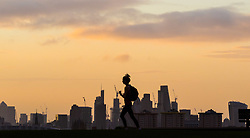 London, September 11 2017. A runner on Primrose hill makes a silhouette against the London skyline as a new day breaks over the city. © Paul Davey