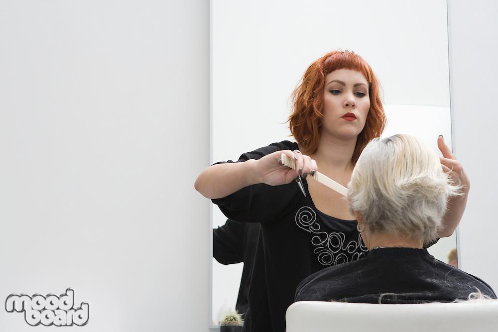 Stylist combs elderly woman's fringe