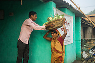 Vegetable farmer Geeta Devi (in orange), 45, a member of a Farmer's Producer Group, sells her harvested cauliflower vegetables at the collection centre in Machahi village, Muzaffarpur, Bihar, India on October 27th, 2016. Non-profit organisation Technoserve works with women vegetable farmers in Muzaffarpur, providing technical support in forward linkage, streamlining their business models and linking them directly to an international market through Electronic Trading Platforms. Photograph by Suzanne Lee for Technoserve