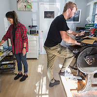 Joyce Li, owner of Onyx Press, and her boyfriend Blake McCollum work together to print birthday invitations at the print workshop in Amory. Li does all of the creative process, including the design, ordering the plate, mixing the ink colors and lining up the plates for the correct print. McCollum helps run the printing press, feeding in the paper and hand-powering the press.