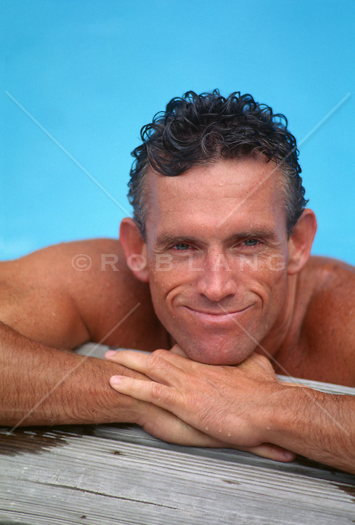 Man leaning on the edge of a swimming pool deck
