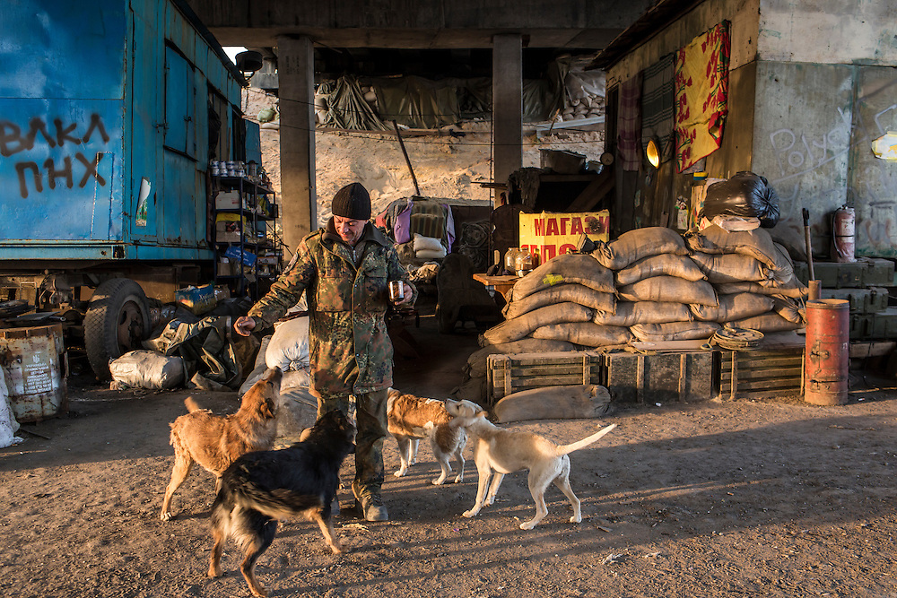 PERVOMAISKE, UKRAINE - MARCH 20, 2015: A fighter who uses the name Capitan plays with some of the dogs that frequent a base of the pro-Ukrainian Dnipro-1 battalion known as The Bridge near ongoing battles for the town of Pisky in Pervomaiske, Ukraine. CREDIT: Brendan Hoffman for The New York Times
