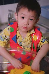 Portrait of nursery school boy wearing apron helping to clean toys in large wash basin,