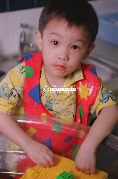 Portrait of nursery school boy wearing apron helping to clean toys in large wash basin,