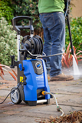 Cleaning paving on a patio with a pressure washer