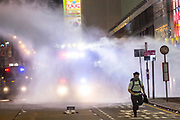 HONG KONG: Sunday 20 October 2019 A protester runs away from a water cannon as it sprays blue dye and water laced with tear gas during clashes in Honk Kong on Sunday. Hundreds of thousands of protesters marched through the city's streets in defiance of the march being denied permission to take place as demonstrations roll into a 14th week. <br /> Rick Findler / Story Picture Agency