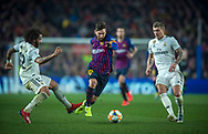 Leo Messi of FC Barcelona passes between Marcelo (left) and Kroos of Real Madrid,during the first match of the Spanish King's Cup semifinal at Camp Nou Stadium in Barcelona,Spain,6 February 2019