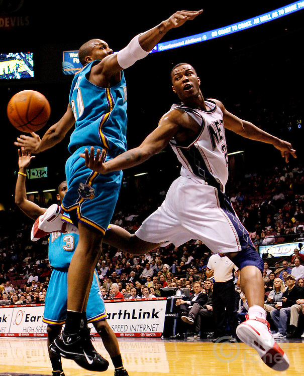 epa00938761 The Nets' Antoine Wright (R) passes past the Hornets' David West (L) during the second half of the New Orleans/Oklahoma City Hornets' 111-107 victory over the New Jersey Nets at Continental Airlines Arena in East Rutherford, New Jersey, Wednesday 21 February 2007.  EPA/JUSTIN LANE
