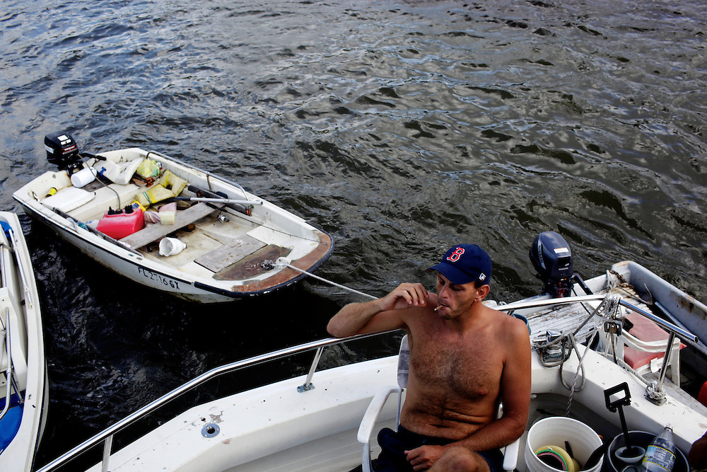 Kenny Canaday, one of the newcomers to the community of people living on their boats in Estero Bay, has a cigarette while hanging-out on the back of Randy Eibler's boat. Canaday has only been living on his sailboat for the past four months and eventually plans to sail to Australia in his watercraft.