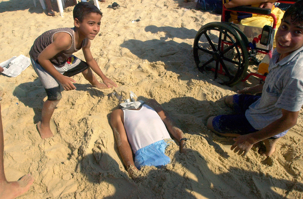 Palestinian children play burying a boy under the sand of the Mediterranean coast of Gaza City in the Gaza Strip Friday July 27, 2001. Despite the 11 months of violence Israelis and Palestinians take a break to enjoy the Mediterranean beaches and the Dead Sea, where under growing tensions and in the case of Gaza under closure people try to  make the best of their summer and carry on a normal life.