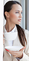 Thoughtful businesswoman having coffee in office