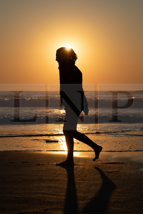 © Licensed to London News Pictures. 26/03/2020. Wadebridge, UK. A walker on Constantine Bay beach, Cornwall during sunset this evening. British Prime Minister Boris Johnson yesterday ordered a lockdown to slow the spread of Coronavirus (COVID-19) across the country. Photo credit : Tom Nicholson/LNP
