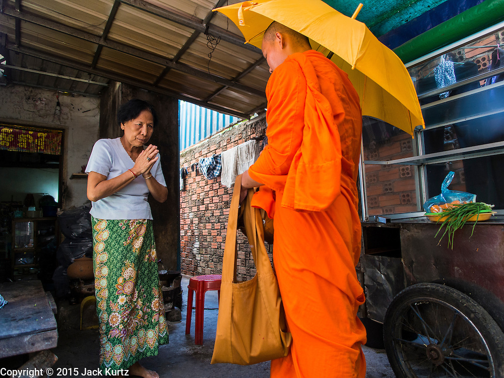 24 FEBRUARY 2015 - PHNOM PENH, CAMBODIA: A woman makes an offering to a Buddhist monk in the White Building. The White Building, the first modern apartment building in Phnom Penh, originally had 468 apartments, and was opened the early 1960s. The project was overseen by Vann Molyvann, the first Cambodian architect educated in France. The building was abandoned during the Khmer Rouge occupation. After the Khmer Rouge were expelled from Phnom Penh in 1979, artists and dancers moved into the White Building. Now about 2,500 people, mostly urban and working poor, live in the building. Ownership of the building is in dispute. No single entity owns the building, some units are owned by their occupants, others units are owned by companies who lease out apartments. Many of the original apartments have been subdivided since the building opened and serve as homes to two or three families. The building has not been renovated since the early 1970s and is in disrepair. Phnom Penh officials have tried to evict the tenants and demolish the building but residents refuse to move out.   PHOTO BY JACK KURTZ