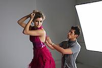 Designer adjusting dress back of fashion model in studio