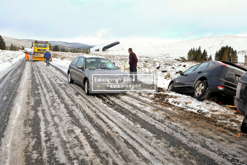 Pictured: <br /> Travellers on the A1701 were willing to lend a hand to help tow a car out of a ditch despite the frozen roads.  Bob Watson was travelling in his Ford Focus from Edinburgh to Moffat when his back wheel dropped into a small pothole, abouit nince miles from the town, which spun his car 180 degrees and into a ditch. His best towing rope was at home and his back up straps were not up to the job when he was getting a tow from Range Rover.  Another set of travellers stoped as they had a tow bar but due to the angle of the car and the ice, the Fopcus only managed to be pulled out about a foot before it bottomed out.  Luckliy a snow plough/gritter stopped and gritted the road to provide purchase for a tow truck with an electric winch to extracate the Focus from the ditch.  Many hands make a difference.<br /> <br /> <br /> Ger Harley   EEm 11 February 2018