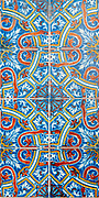 Traditional Portuguese seamless ceramic tiles in blue white red and orange used to decorate the outside walls of houses and buildings. Photographed in Portugal