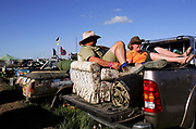 """Festival-goers on a sofa in the back of their ute at the annual Deniliquin Ute Muster in Deniliquin, Australia.A """"ute"""" is a term used in Australia for a utility vehicle, popular in the rural areas and used for farming and other work needs."""