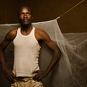 Arouna Ouedraogo (44), a farmer and artisanal gold miner, with his mosquito net in the village of Songodin in the Sanmatenga region of Burkina Faso on 25 February 2014. Mosquito nets greatly decrease the incidence of malaria by reducing the risk of being bitten by the nocturnal Anopheles mosquito, which carries the malaria parasite.