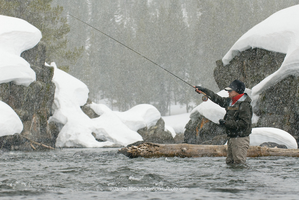 An angler fly fishes for trout during a winter day on the Henry's Fork of the Snake River, Idaho.