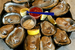 11june 2010. New Orleans, Louisiana. <br /> Oysters at renowned restaurant Arnaud's in the French Quarter. Worries persist as fish stocks run low and prices rise thanks to closed fishing grounds affected by oil pollution. BP's disastrous environmental catastrophe out in the Gulf of Mexico threatens  the livelihood of many thousands of workers affiliated to the fishing industry in Louisiana. Thousands of barrels of oil per day continues to leak into the Gulf because of the explosion and collapse of the Deepwater Horizon drilling platform 46 miles out to sea. The closure of fishing grounds both east and west of the Mississippi river outflow is crippling thousands of local fishermen and all affiliated businesses and families who rely on the seafood industry.  <br /> Photo; Charlie Varley/varleypix.com