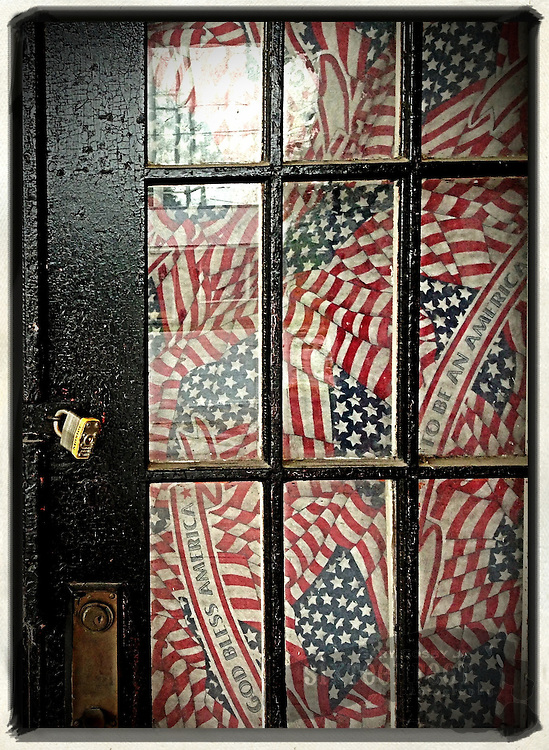 Gary Cosby Jr.  iPhone photographs  A door in Falkville, Alabama shows signs of patriotism with a flag displayed behind the glass panes.
