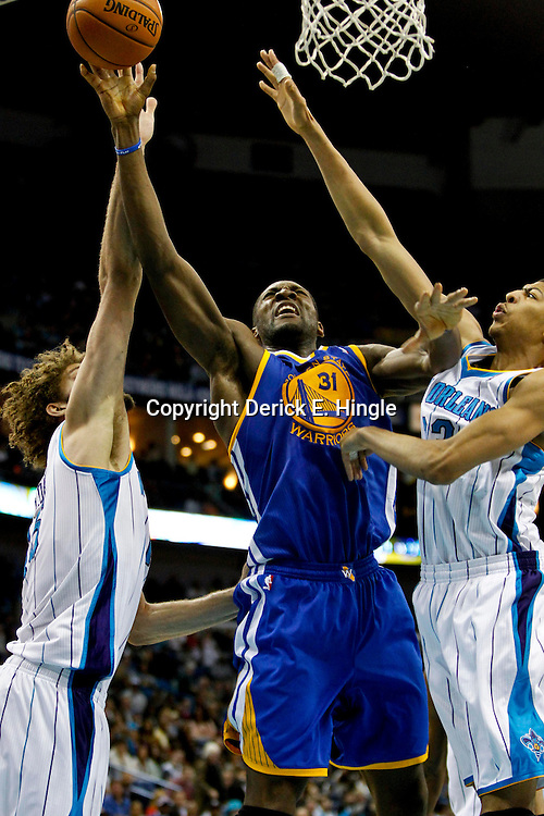 Jan 19, 2013; New Orleans, LA, USA; Golden State Warriors center Festus Ezeli (31) shoots over New Orleans Hornets power forward Anthony Davis (23) and center Robin Lopez (15) during  the second half of a game at the New Orleans Arena. The Warriors defeated the Hornets 116-112. Mandatory Credit: Derick E. Hingle-USA TODAY Sports