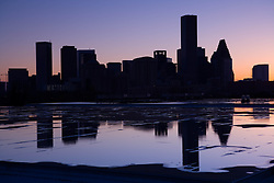Silhouette of the Houston, Texas skyline reflected in a rooftop rain puddle after a storm.