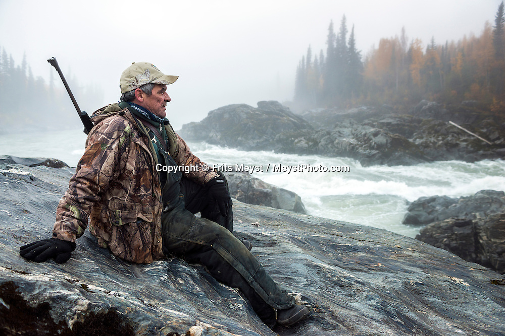 Mayo, Yukon Territory, Canada, September 2014. Frank Patterson, a member of the NND First Nation, on the lookout for his annual moose. Band members of the First Nation of NaCho Nyak Dun return to their traditional fishing spot below the Fraser Falls on the Stewart River to fish for Whitefish and Chum . The nation has agreed to not fish salmon for the duration of a full life cycle of the declining species. So few salmon have reached their traditional spawning grounds that they are threatened by extiction.  Photo by Frits Meyst / MeystPhoto.com