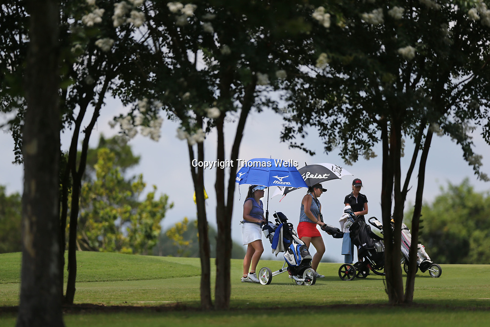 Golfers Riley Mayhew, left, Sarah Johnson break out their umbrella's to sheild themselves from the hot afternoon during their final round of Friday's Pros of Tomorrow tournament.
