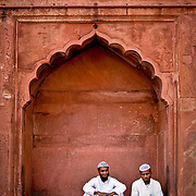 Two men sit and rest in the arch  on the side of the Jamma Masjid.