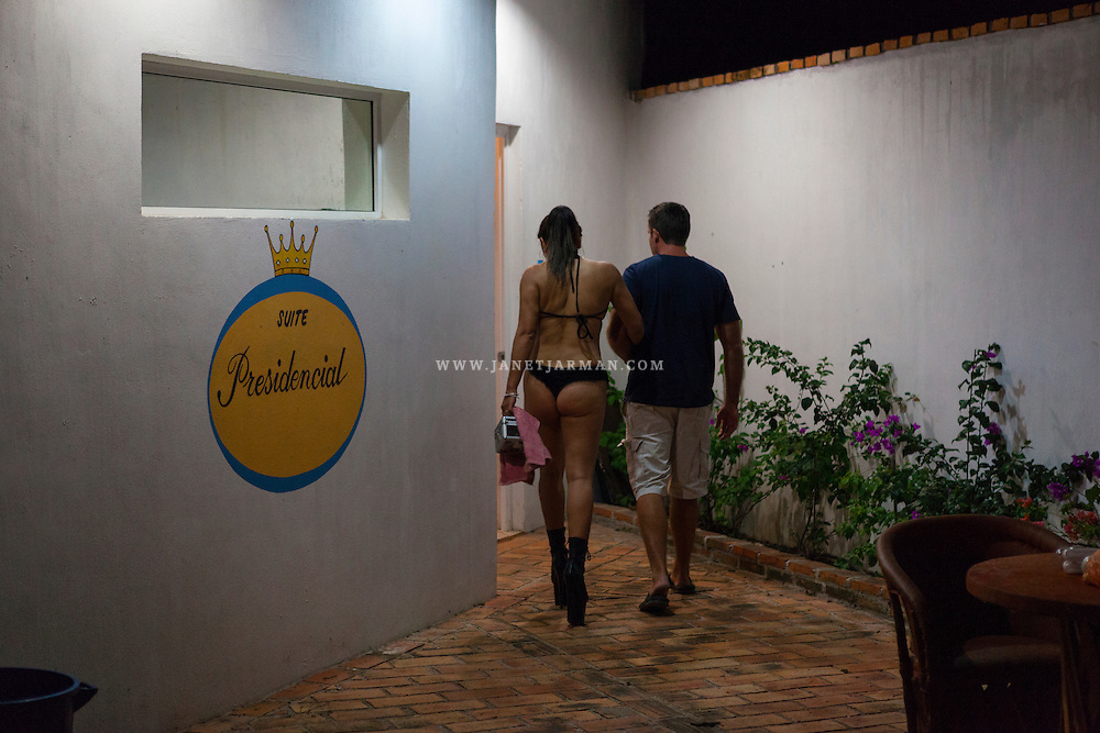 """An exotic dancer named Andrea guides a client into the """"Presidential Suite"""" at Oasis, a night club that opened briefly in a small town on Mexico's Pacific Coast but closed down after just three days."""