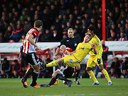 Nottingham Forest striker Jamie Ward  being taken out by Brentford midfielder Alan McCormack during the Sky Bet Championship match between Brentford and Nottingham Forest at Griffin Park, London, England on 21 November 2015. Photo by Matthew Redman.