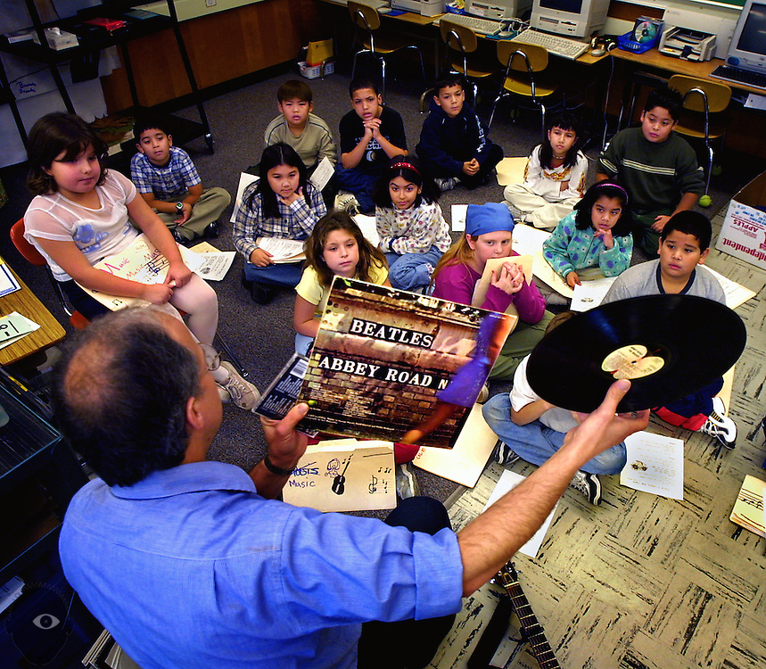Success in the classrooms at Woodmere Elementary School includes visits by music teacher Paul Colvin, here introducing them to the Beatles in record form.