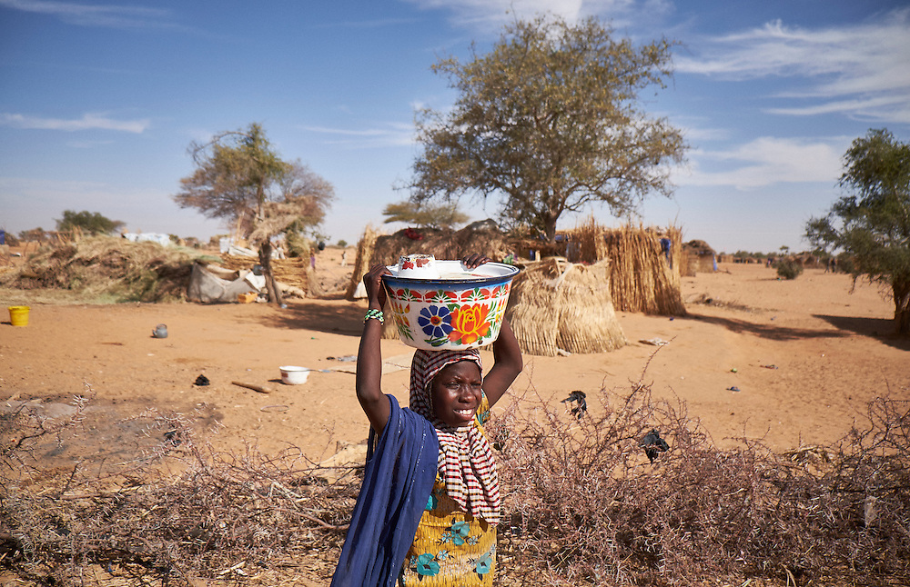 A girl walks through a camp of internally displaced people near the village of Kouble by the side of the road on the highway outside of Diffa, Niger on February 17, 2016. The camp is made up of displaced people and refugees from villages along the border between Niger and Nigeria and who fled attacks from Boko Haram.