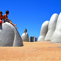 Boys Sitting on La Mano, The Hand, on Brava Beach in Punta del Este, Uruguay<br />
