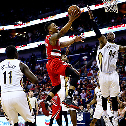 Mar 18, 2016; New Orleans, LA, USA; Portland Trail Blazers guard Damian Lillard (0) shoots over New Orleans Pelicans forward Dante Cunningham (44) and guard Jrue Holiday (11) during the second quarter of a game at the Smoothie King Center. Mandatory Credit: Derick E. Hingle-USA TODAY Sports