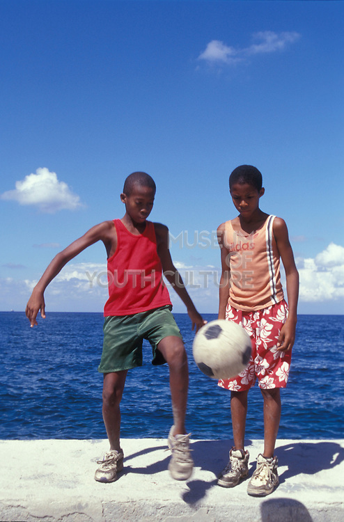 Two boys standing on a wall kicking a football on a sea front, Havana, Cuba, 2000's