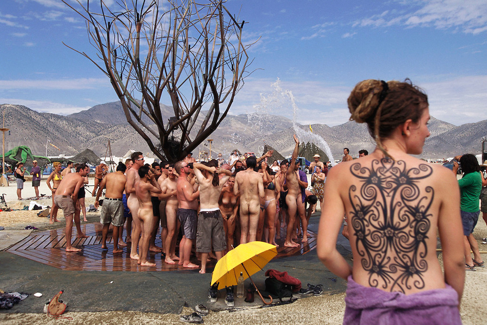 "People showering at ""The One Tree"", a metal tree that has gas flames in the branches at night at Burning Man festival..Burning Man is a performance art festival known for art, drugs and sex. It takes place annually in the Black Rock Desert near Gerlach, Nevada, USA.."