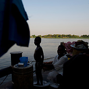 A woman baths her son aboard a barge docked in Juba port. Thousands of South Sudanese families left the north in direction to the south, a journey that for some takes months, in the hope to start a new life in the new country.