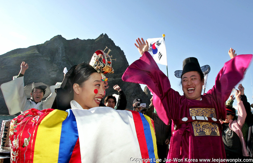 "South Korean Kim Jong-bok (R) gives three patriotic cheers as his bride Song Hee-jung (front L) looks on during their traditional wedding ceremony on the Dokdo islets off the Korean peninsula April 23, 2005. Song Kyung-chan (back L), the captain of the Sambong-ho, which plies between Ulungdo and Dokdo, officiated at the wedding. Traditional martial arts performer Kim and stage actress Song held the first-ever wedding on Dokdo, organised by local online companies, to protest against Japan's claim over the islets, which Japan calls ""Takeshima"". /Lee Jae-Won"